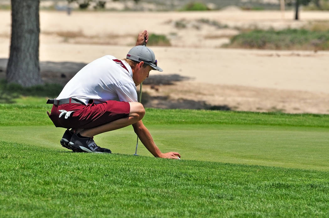 Austen Ancell lines up a putt at the end of last season. The team will need him and his leadership this year if they want to go to state.  Horace Langford Jr / Pahrump Valley Times
