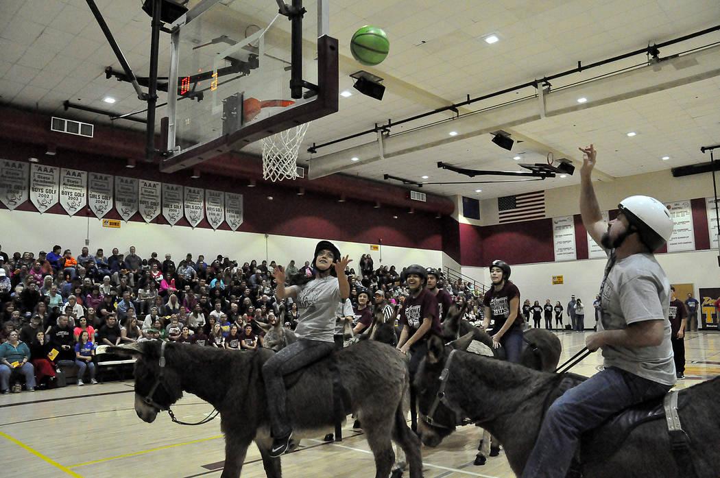 High school teacher Angelica Schuerger, left, makes sure that fellow teacher Dylan Moellendorf's shot goes in. The high school team won their game against high school seniors but didn't advanc ...