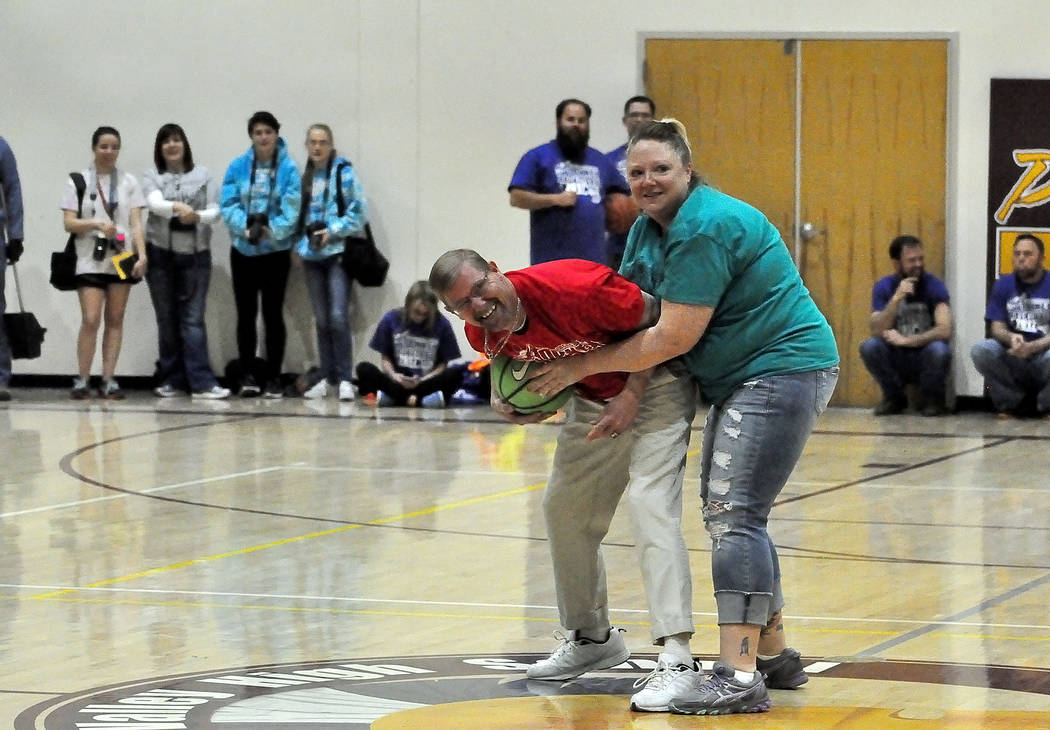 Rosemary Clarke Middle School social worker Alicia Lewis gives the whole wrap-around play a try against an unsuspecting elementary school staff member. Is that legal? It is in donkey basketball. H ...