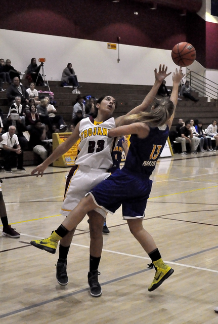 Isabelle Meza (23) goes for a rebound against the Pirates on Tuesday. Meza was the leading scorer for the Lady Trojans with 15. Horace Langford Jr. / Pahrump Valley Times
