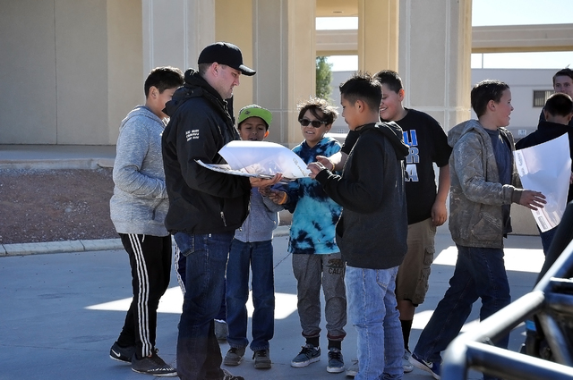 Horace Langford Jr. / Pahrump Valley Times Students at RCMS gather around  Jason Coleman, a Pahrump Nugget 250 race driver, as he hands out posters to the kids. The RPM Off-road racing team of Cly ...