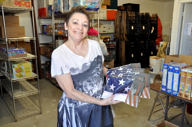 Kathy Gnecco stands with new flags donated to replace old worn flags. The VFW will hold a flag exchange during this month. The VFW post is located at 4651 Homestead Road and the dates for the exch ...