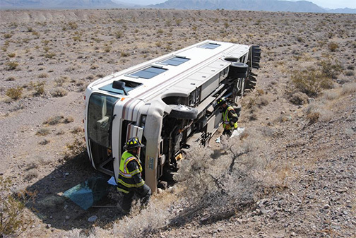 Pahrump firefighters inspect a full-size motorhome which rolled more than 30 feet down a steep embankment along west Bell Vista Road near the Ash Meadows junction. The driver, who was the sole occ ...