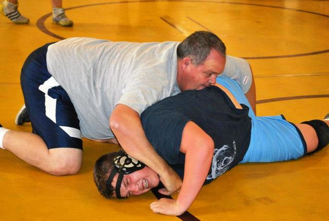 Charlotte Uyeno / Pahrump Valley Times Kyle Daffer wrestles with his father Marty Daffer. Marty Daffer was on the first wrestling team the Trojans ever had post 1974. Kyle Daffer graduated in 2014.