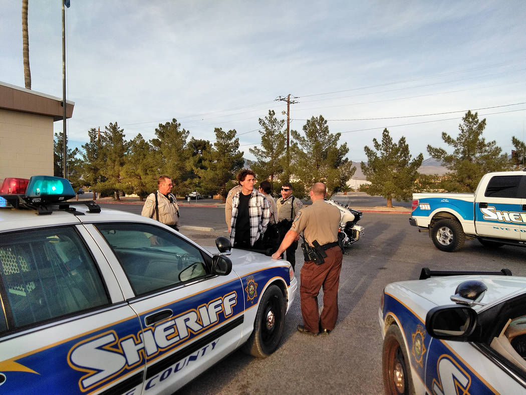 Selwyn Harris/Pahrump Valley Times  Nye County Sheriff's Deputies speak to Pahrump resident James Lewis Fritts, 19, who was arrested and charged for throwing a rock at a marked sheriff's offic ...