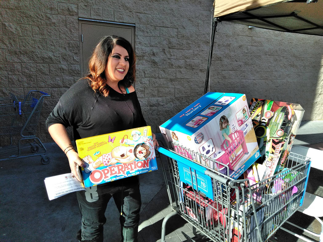 Selwyn Harris/Pahrump Valley Times Pahrump Disabilities Outreach Program co-founder Stephanie Lopez stands before a cart full of toys collected on Saturday outside of Walmart. The toys will be dis ...