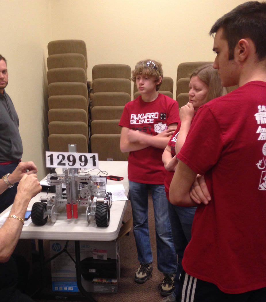 Special to the Pahrump Valley Times Coach Adam Lightfoot, Builder Zeke Hall, Coach Ashley Hall, and Artist/Modeler Landon Ingersoll meet with the judge to get feedback on their robot's design.