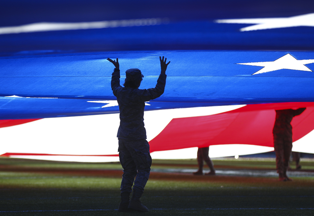 Chase Stevens/Las Vegas Review-Journal Members of the military present the flag at the start of the Las Vegas Bowl at Sam Boyd Stadium in Las Vegas on Saturday, Dec. 17, 2016.