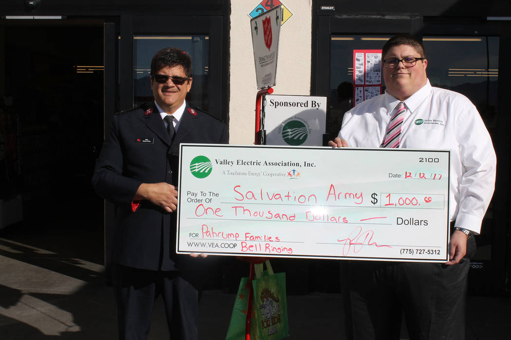Special to the Pahrump Valley Times  Salvation Army Major Mario Ruiz (left) was front of Smith's to receive the check from Ryan Muccio, VEA community relations representative. In addition to the v ...
