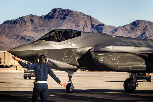 Jeff Scheid/Las Vegas Review-Journal A flight line member directs at F-35 Lightning II stealth fighter jet at Nellis Air Force Base in 2015.  The high-tech F-35 joint strike fighter jet is the U.S ...
