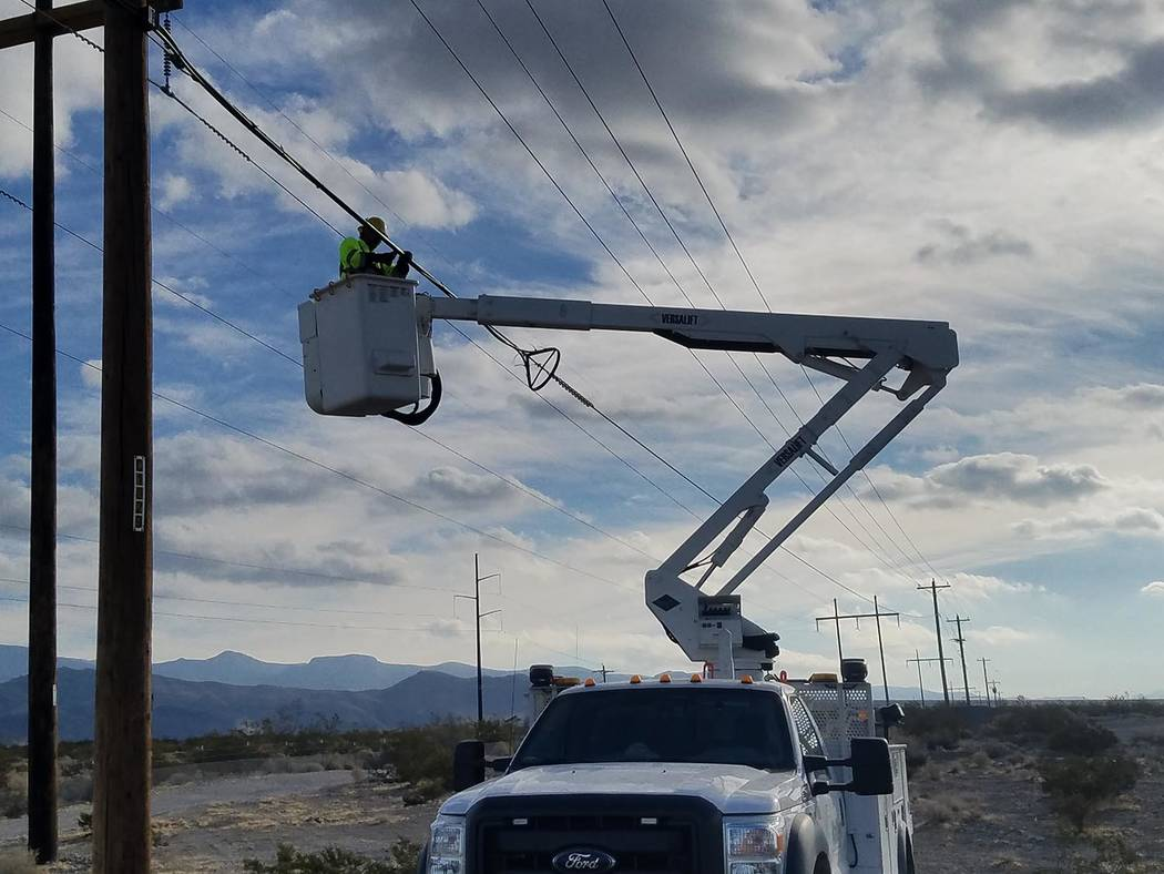 David Jacobs/Pahrump Valley Times A crew member for Valley Communications is shown working in Nye County earlier this fall. VCA plans to hang fiber on its power poles from the Sandy Valley turnoff ...