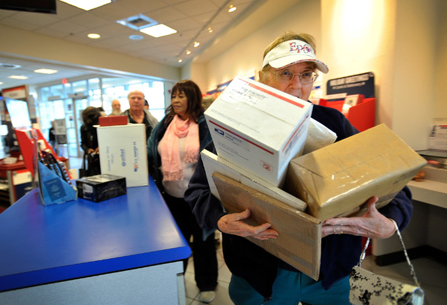 David Becker/Las Vegas Review-Journal A customer struggles to carry packages to the counter at a U.S. Post Office as shown in this file photo. About 200 million packages are estimated to be delive ...