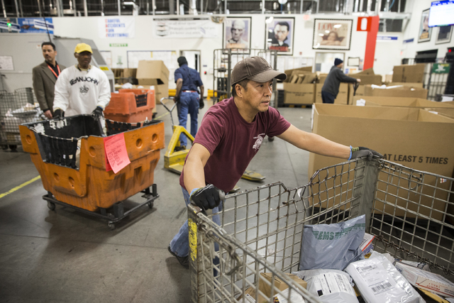Benjamin Hager/Las Vegas Review-Journal  A postal worker rolls a large bin of mail to be sorted at the Las Vegas Mail Processing Annex ahead of the 2016 Christmas rush as shown in this file photo.
