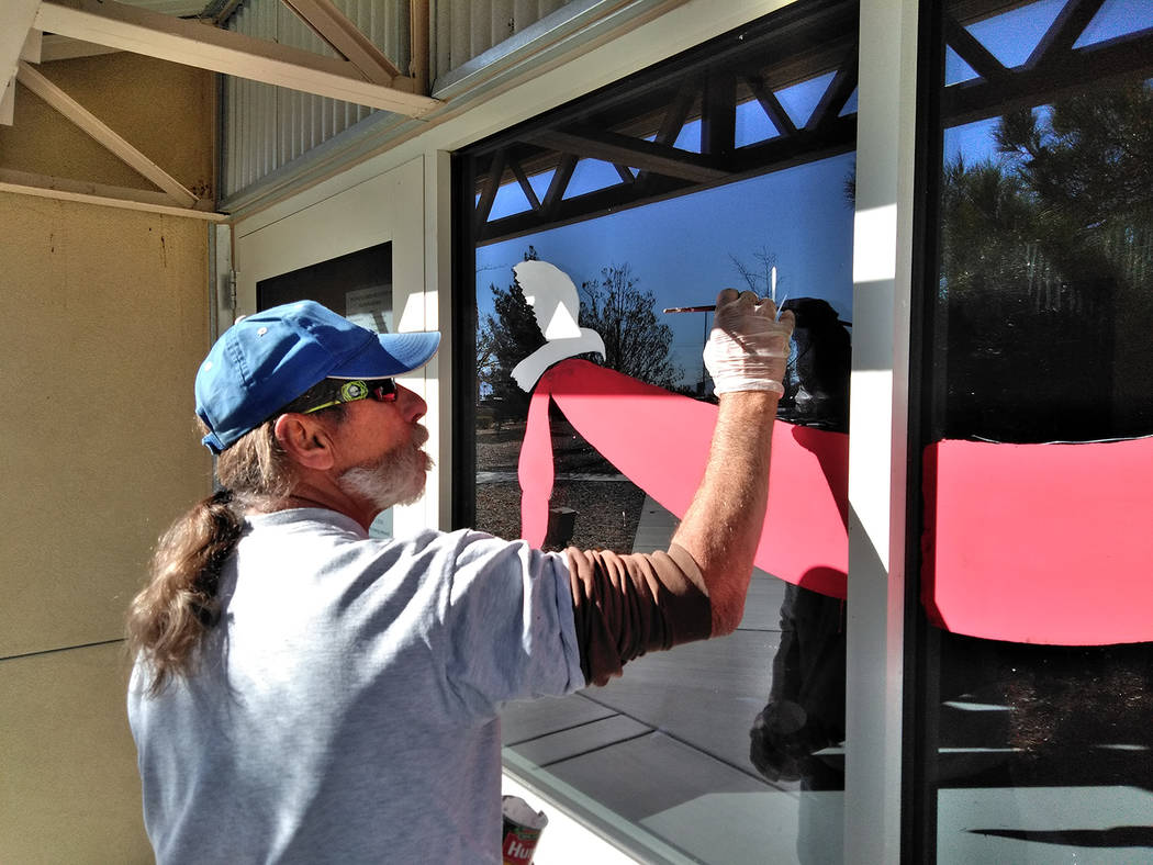 "Selwyn Harris/Pahrump Valley Times  As a professional holiday window artist, Douglas ""Dok"" Hembree adds some holiday pizzazz to a window pane at the Ian Deutch Government Complex on East Basin ..."