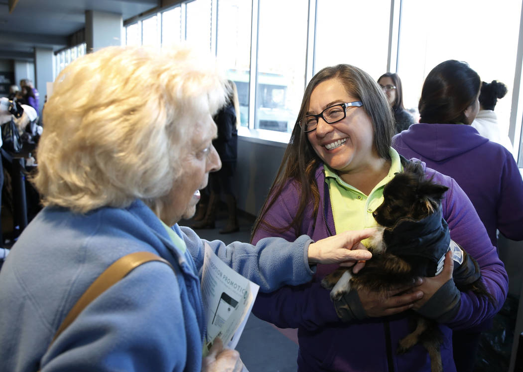 Sandy Colins, left, pets Hat Trick as Mary Brittsan, a volunteer at the Animal Foundation, looks on at City National Arena Monday, Dec. 18, 2017, in Las Vegas. The Vegas Golden Knights and the Ani ...