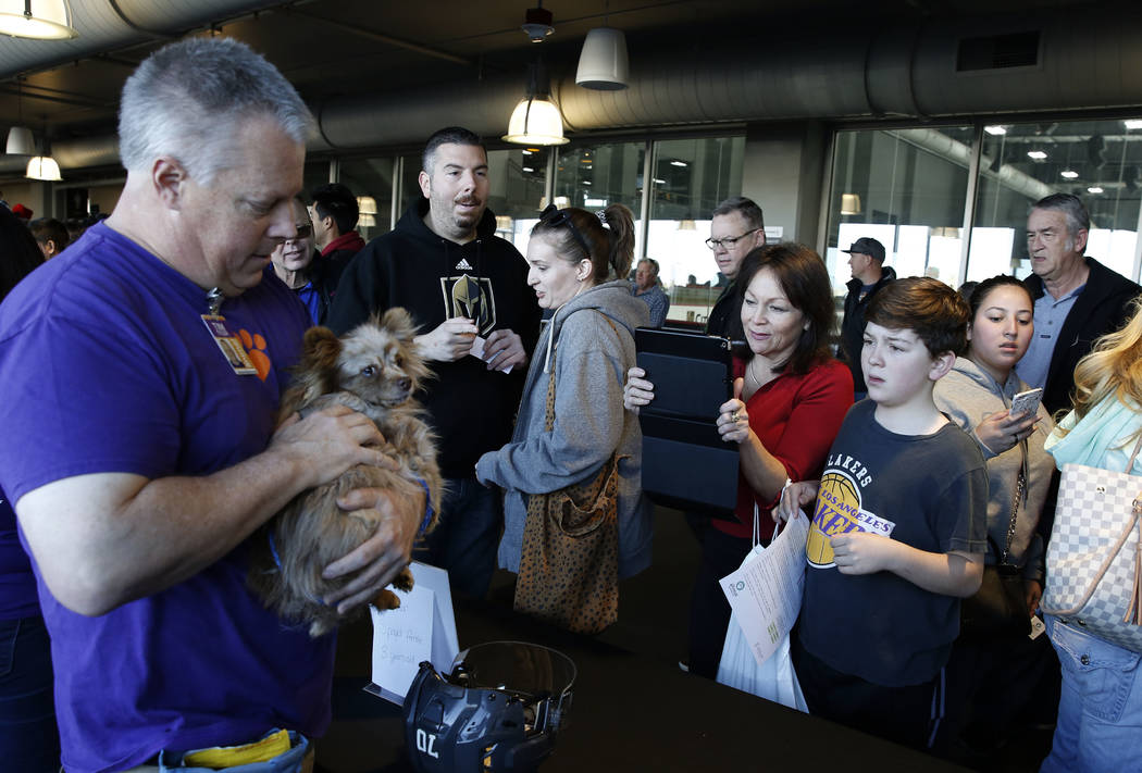 Tim Tyler holds Feather as Wanda Juzefczyk and her son Harry, 12, look on at City National Arena Monday, Dec. 18, 2017, in Las Vegas. The Vegas Golden Knights and the Animal Foundation held a Puck ...