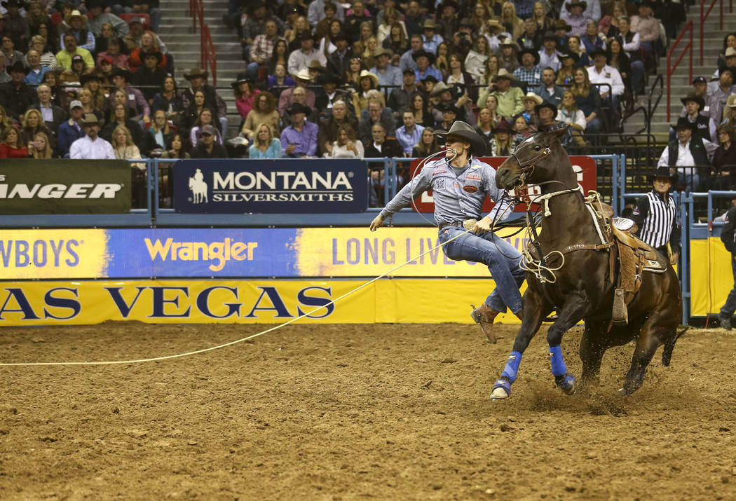 Tuf Cooper of Weatherford, Texas takes part in the tie-down roping competition in the tenth go-round of the National Finals Rodeo, Saturday, Dec. 16, 2017, at the Thomas & Mack Center in Las V ...
