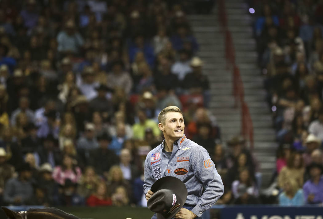 Tuf Cooper of Weatherford, Texas looks on after taking part in the tie-down roping competition in the tenth go-round of the National Finals Rodeo, Saturday, Dec. 16, 2017, at the Thomas & Mack ...