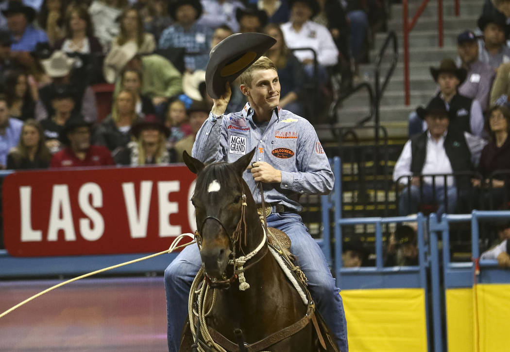 Tuf Cooper of Weatherford, Texas waves to the crowd after taking part in the tie-down roping competition in the tenth go-round of the National Finals Rodeo, Saturday, Dec. 16, 2017, at the Thomas  ...