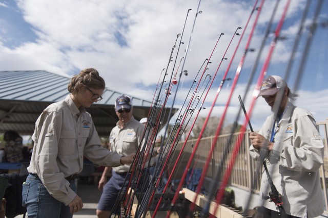 Jason Ogulnik/Las Vegas Review-Journal Jessica Brooks, conservation education coordinator with the Nevada Department of WIldlife, left, sorts fishing rods and reels during a fishing derby last yea ...