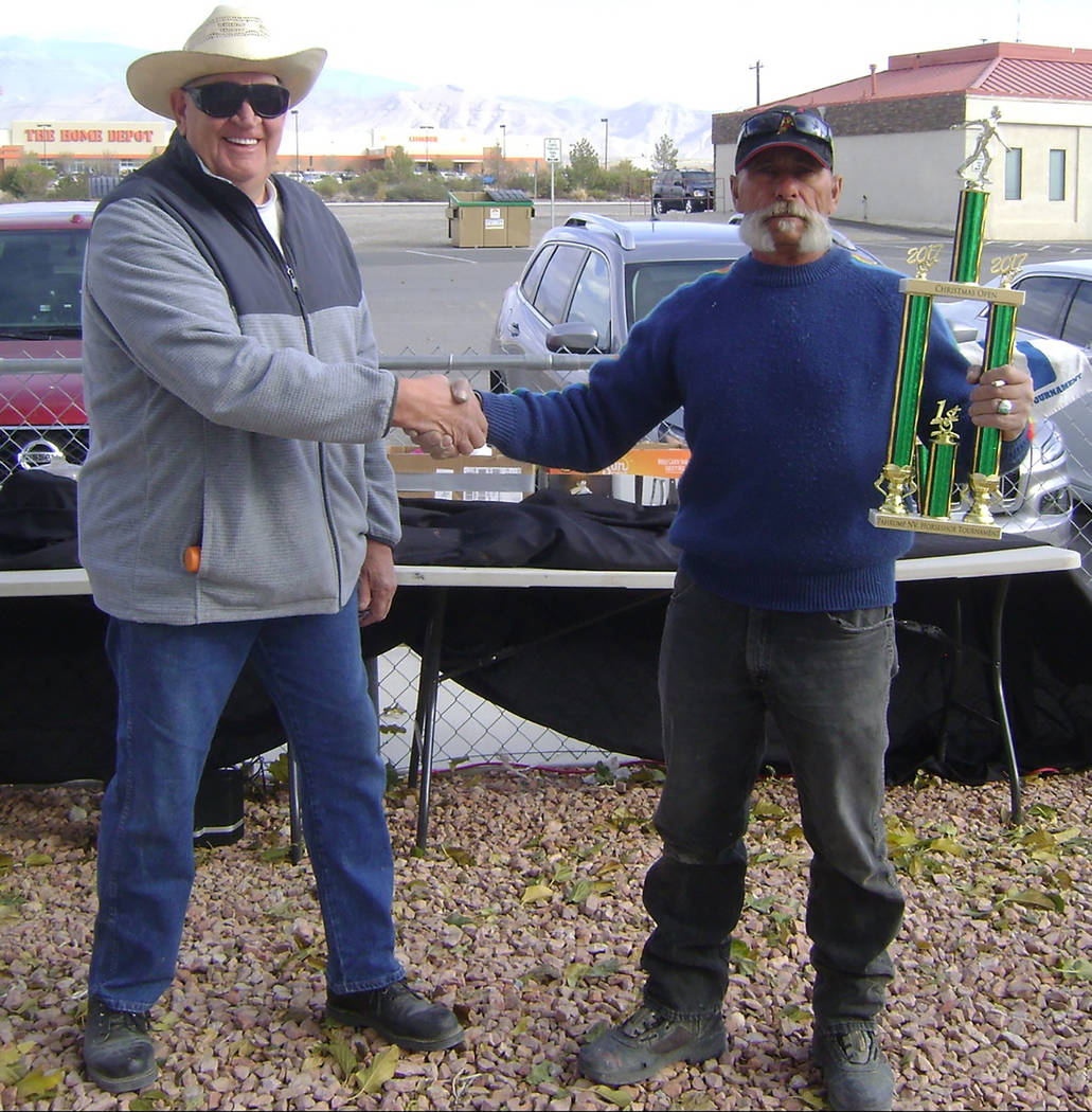 Special to the Pahrump Valley Times Dennis Andersen is shown presenting a trophy to Dok Hembree. Hembree was among those earning first-place honors in the Pahrump horseshoe tournament on Dec. 16.