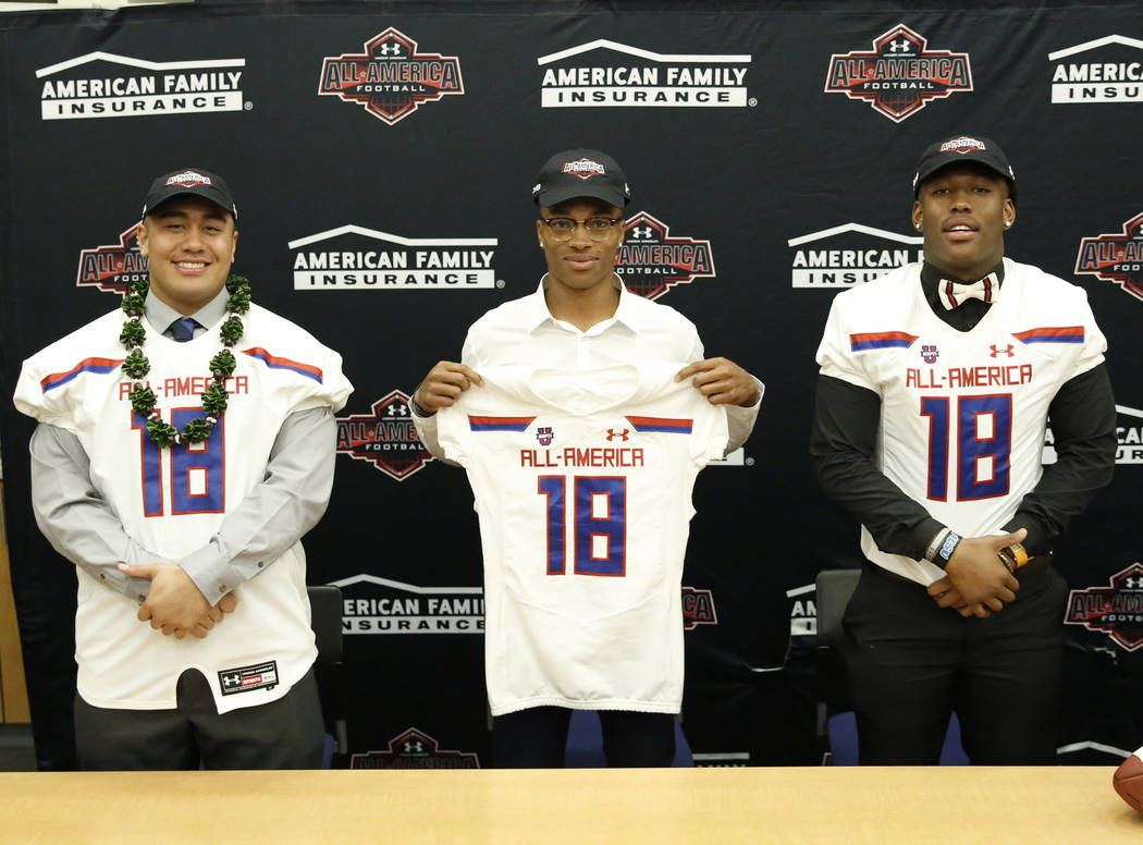 Bishop Gorman's offensive guard Jacob Isaia, left, quarterback Dorian Thompson-Robinson and tight end Brevin Jordan, right, receive their honorary All America Game jersey at their school Wednesday ...
