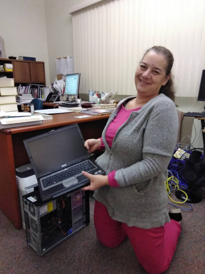 Selwyn Harris/Pahrump Valley Times  Pahrump Community Library Reference Clerk Amy Bruno holds an old laptop computer destined to be recycled on Saturday Jan. 6. Officials from Nevada State Recycle ...