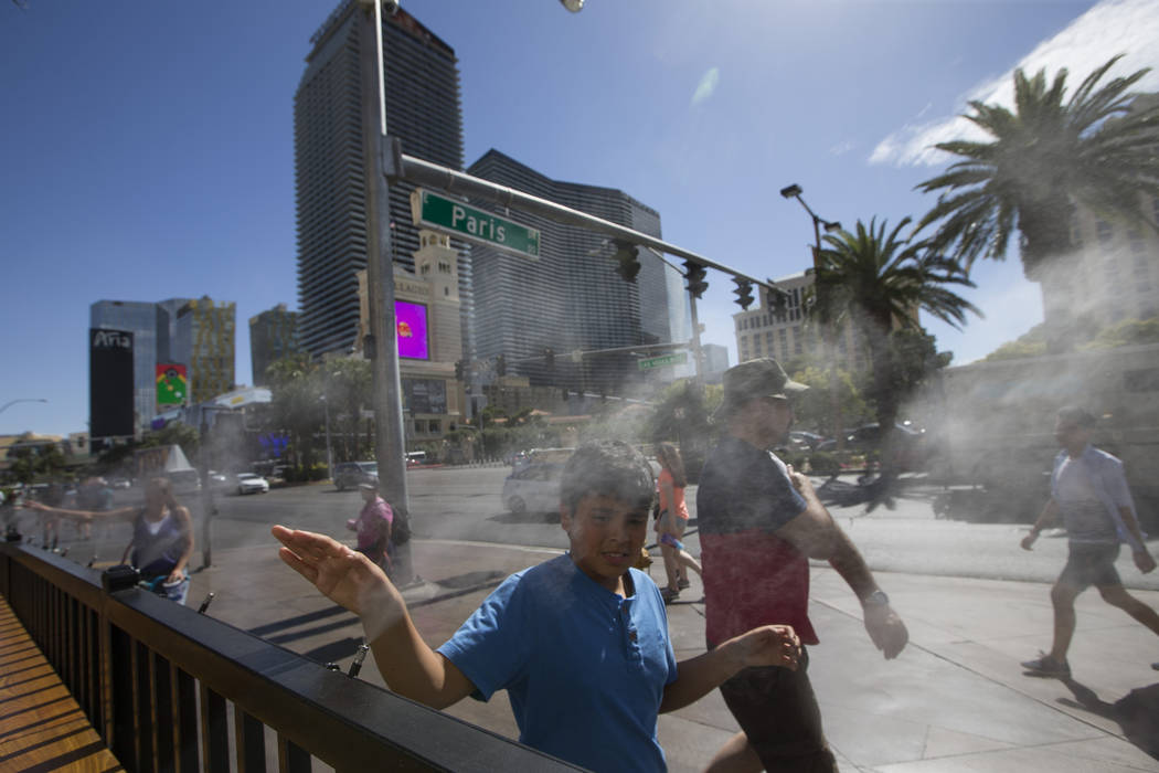 Richard Brian/Special to the Pahrump Valley Times Pedestrians cool off on water misters along Las Vegas Boulevard in Las Vegas on Thursday, May 25, 2017. The Las Vegas Valley registered its hottes ...