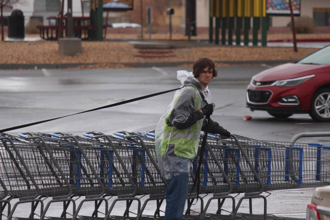 Jeffrey Meehan/Pahrump Valley Times Employee at the Pahrump Walmart pushes carts through a wet parking lot, as rain returns to the Pahrump Valley after 116 days without precipitation. The stretch  ...