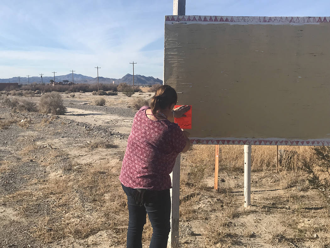 A representative of Nye County Code Enforcement is pictured placing a warning notice on one of the many signs that have been erected in Pahrump that do not adhere to Nye County Code. Sign owners w ...