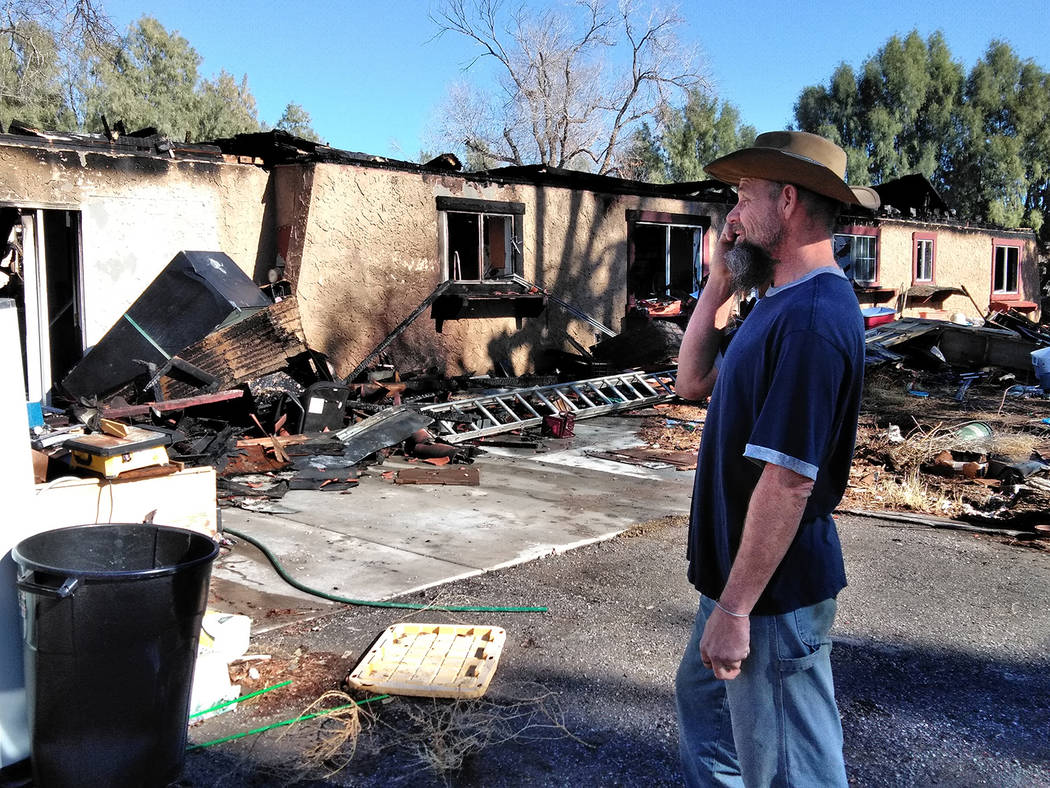 Selwyn Harris/Pahrump Valley Times  Pahrump resident Royal Cutler surveys the destruction of his family's home the day after a devastating fire ravaged the Manse Road residence on Jan. 10. At le ...