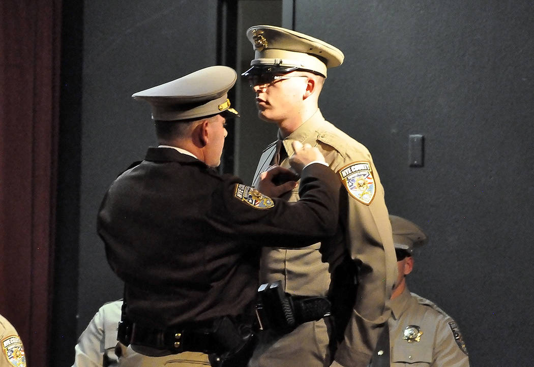 Horace Langford Jr./Pahrump Valley Times Nye County Undersheriff Michael Eisenloffel pins a replica sheriff's office badge on the lapel of his son Theodore during the graduation ceremony on Saturd ...