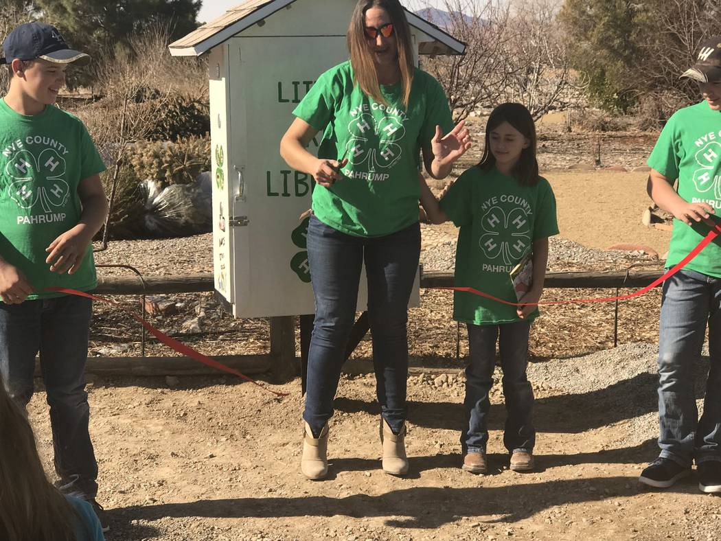 Jeffrey Meehan/Pahrump Valley Times Jamie Domina, a leader at Pahrump 4-H, cuts the ribbon to a Little Free Library, where people can exchange a book for another title at the library. The structur ...