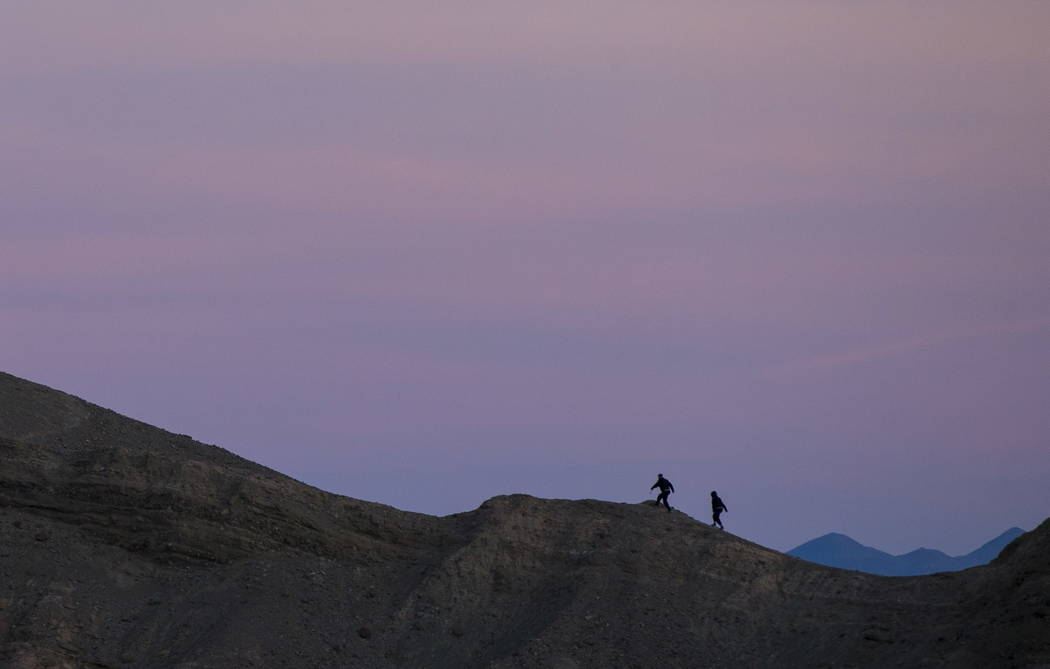 Chase Stevens/Las Vegas Review-Journal  People, seen looking east from Zabriskie Point, make their way up a ridge before sunset in Death Valley National Park, California, on Wednesday, Jan. 24, 2018.