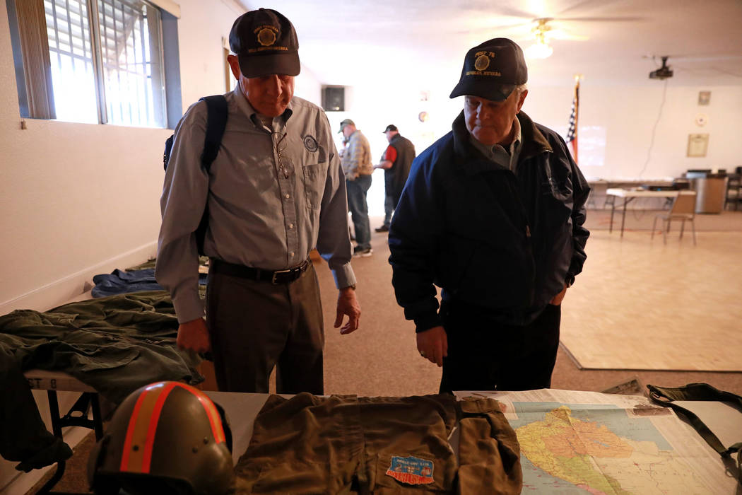 Veterans Stephen Daugherty, left, and Joel Forman look at different war memorabilia during a 50th anniversary event remembering the Vietnam War Tet Offensive at the American Legion Vegas Post 8 in ...