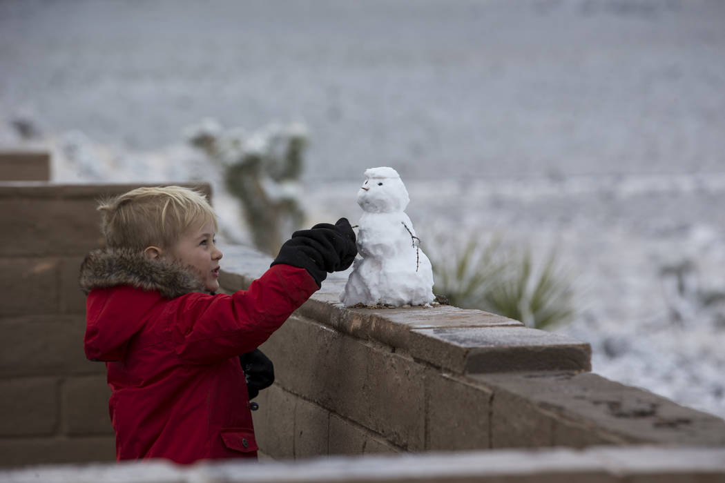 A boy looks at a snowman at Red Rock Canyon Overlook on Friday, Feb. 23, 2018. Richard Brian Las Vegas Review-Journal @vegasphotograph