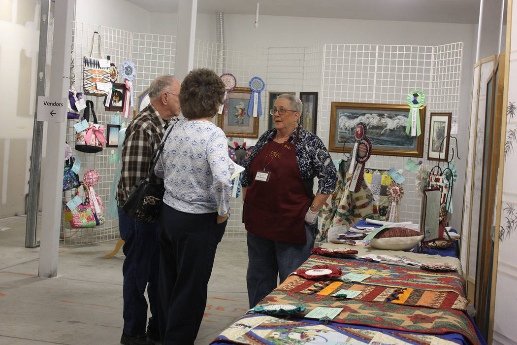 Robin Hebrock/Pahrump Valley Times Pins and Needles Quilt Show volunteer Debi Rodriguez chatted with patrons in the area dedicated to non-quilt entries, such as the table runners, purses and other ...