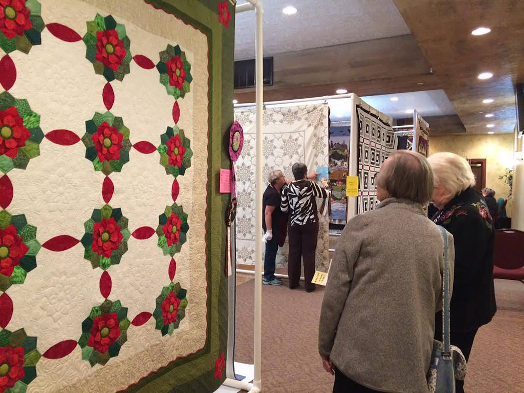 "Robin Hebrock/Pahrump Valley Times This piece took home a second place award for medium long-arm quilting and Best Machine Quilting. Darla Holt created this quilt, which she called ""Blooming Dresd ..."