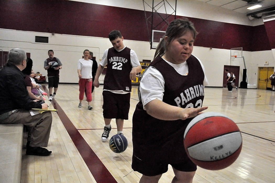 Horace Langford Jr./Pahrump Valley Times Kellye Dorrough (33) and Lucas Mont-Ros (22) participate in a dribbling drill followed by skills coach Amber Ames during Special Olympics basketball practi ...