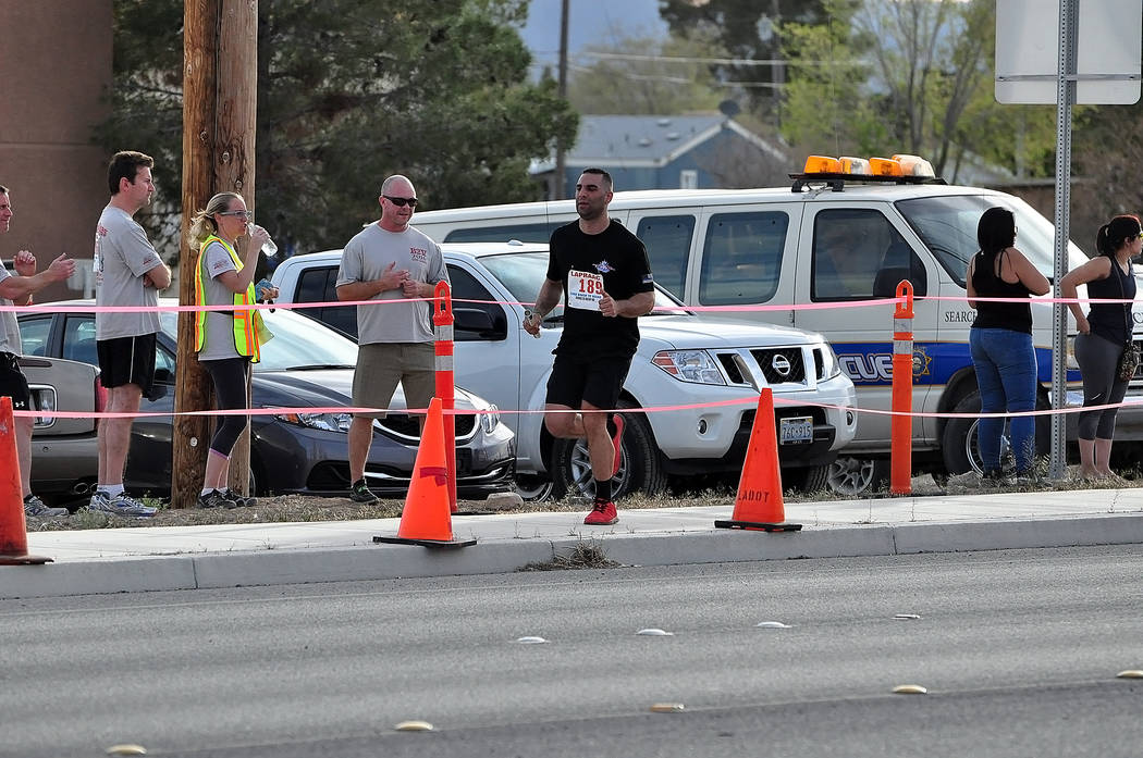 Horace Langford Jr./Pahrump Valley Times An Orange County, California, Sheriff's Department runner reaches the exchange point at state Route 372 and Blagg Road during last year's Baker to Vegas Ch ...