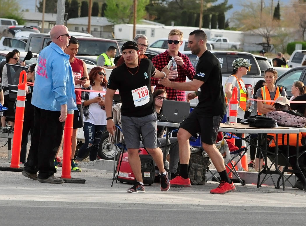 Horace Langford Jr./Pahrump Valley Times A Stage 10 runner passes the baton to his Stage 11 teammate with the Orange County, California, Sheriff's Department during the 2017 Baker to Vegas Challen ...