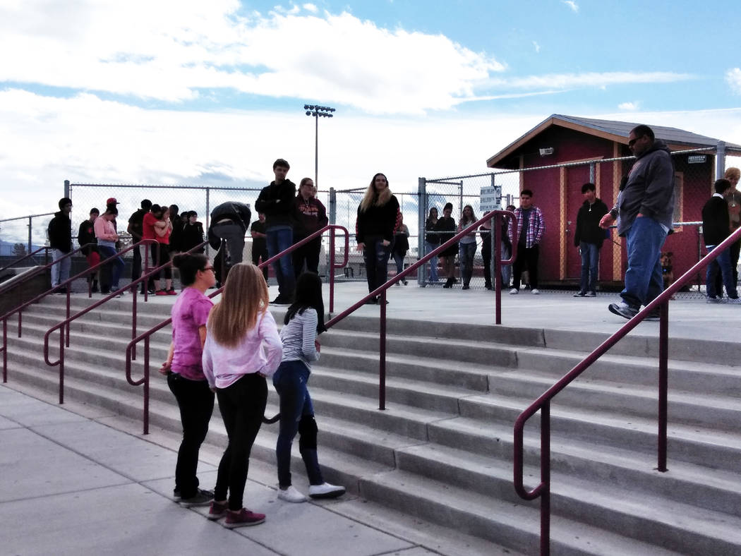 Selwyn Harris/Pahrump Valley Times High school students at Pahrump Valley High School stand around the steps of the school's football field on March 14, 2018. Less than 100 students participated i ...