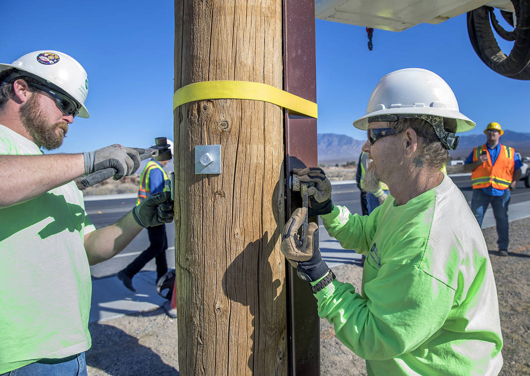 Valley Electric Association VEA Apprentice Lineman Schain Thomson, left, works with VEA Journeyman Lineman Cory Parker to bolt the steel reinforcement to a power pole after it had been driven into ...
