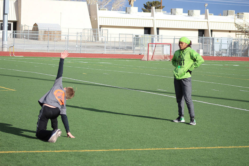 """Tom Rysinski/Pahrump Valley Times Dominique Maloy watches as Dane Clayton, 11, goes through stretching exercises at her """"A Youth Sports Experience"""" sports camp on March 17 at Pahrump Valley High S ..."""