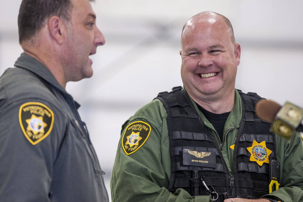 Bryan Woolard, a helicopter pilot, right, laughs with Chief Pilot Steve Morris Jr. before unveiling the new Las Vegas police helicopter at the North Las Vegas Airport on Aug. 16, 2017. (Patrick Co ...