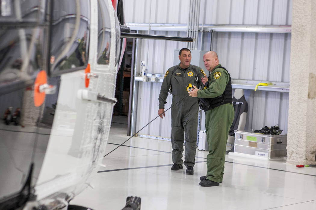Chief Pilot Steve Morris Jr., center,  and pilot Bryan Woolard prepare the new Las Vegas police helicopter for flight at the North Las Vegas Airport on Aug. 16, 2017. (Patrick Connolly/Las Vegas R ...