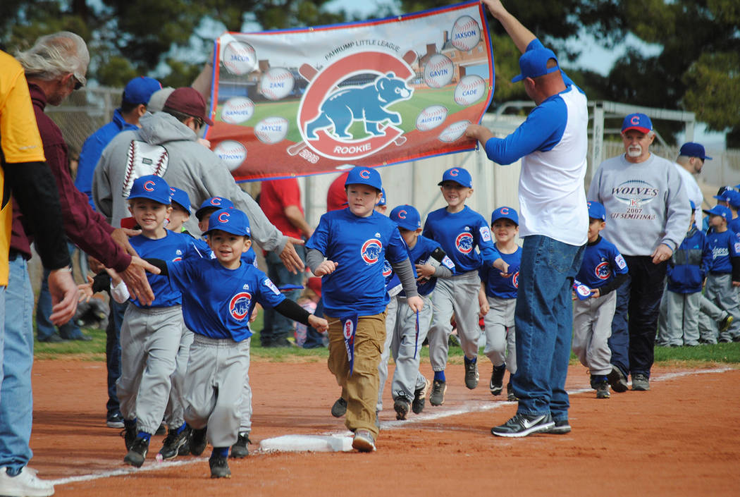 Charlotte Uyeno/Pahrump Valley Times Rookie Cubs run down the first-base line, banner and all, during the P-Town Little League Opening Day ceremonies March 24 at Ian Deutch Memorial Park.
