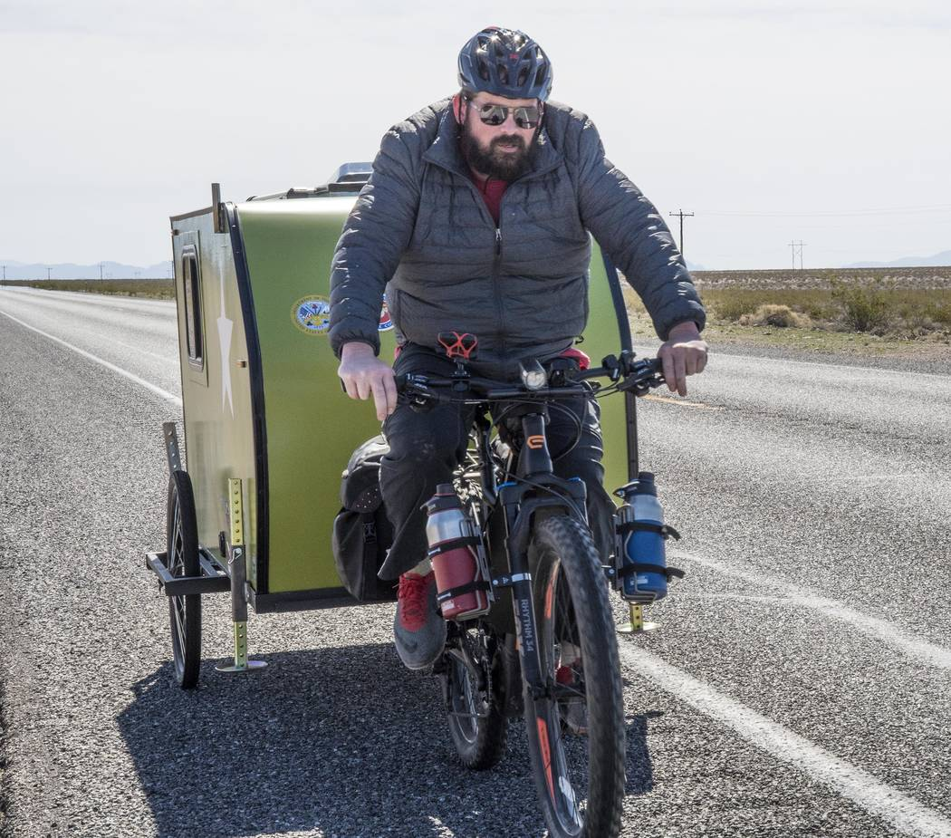 Richard Stephens/Special to the Pahrump Valley Times Eli Smith pedaling between Lathrop Wells and Beatty before the hit-and-run crash. Smith, an Army veteran, is traveling the four corners of America.