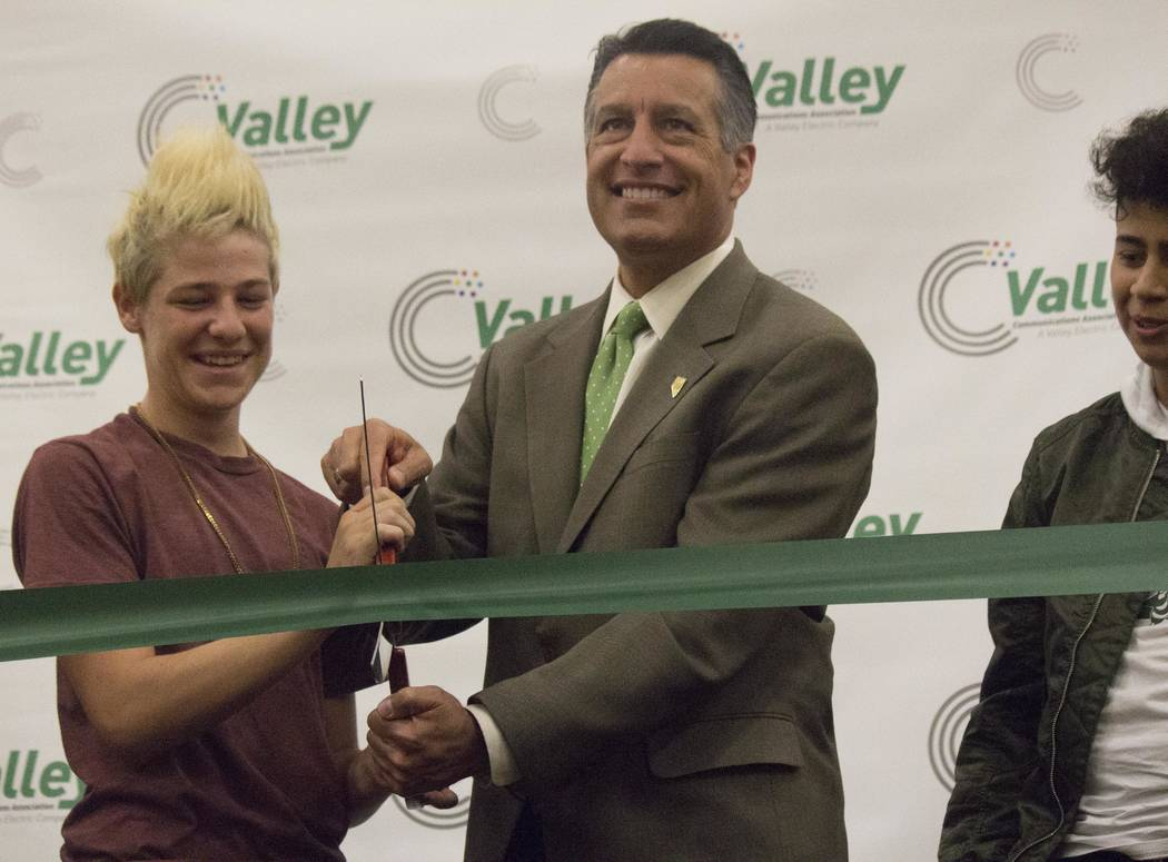Jeffrey Meehan/Pahrump Valley Times Gov. Brian Sandoval, and two unidentified students, cut a green ribbon during an event at Beatty High School recognizing the town to be the first all fiber-opti ...