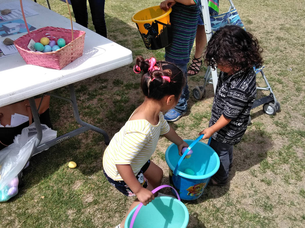 Selwyn Harris/Pahrump Valley Times Siblings help one another amass as many eggs as possible while traipsing around Petrack Park during Saturday's Community Easter Picnic. The free event, was hoste ...